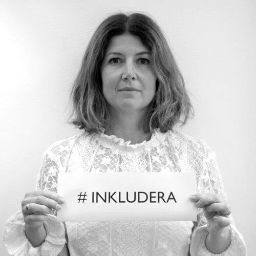 Martina Högberg i svartvitt foto, håller i en skylt som det står inkludera på