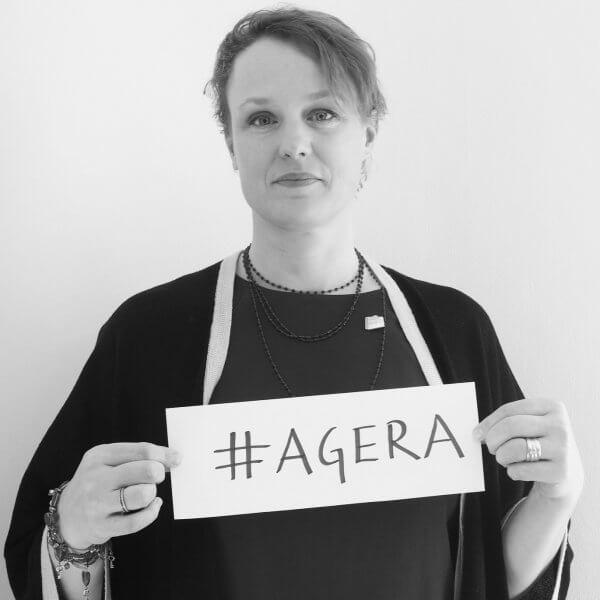 """Foto på Cecilia Åhlberg, hållandes en skylt med texten """"agera"""""""