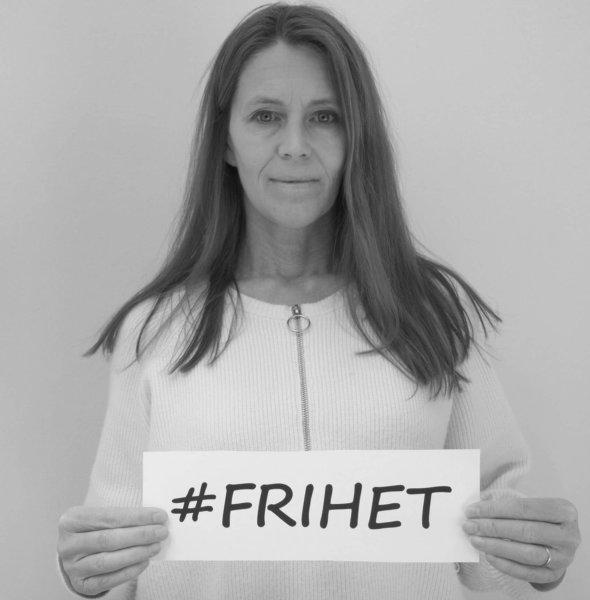 Bild på Inger som håller upp en skylt med texten Frihet